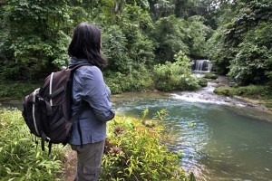 A female hiker in the interior of Nias Island, looking at Luaha N'ndroi Waterfall in Alasa sub-district of North Nias, Indoneisa. Ecotourism.