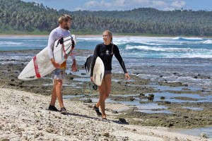 Surfing couple walking with their surboards on Pasir Beach, North-West Nias Island, Indonesia