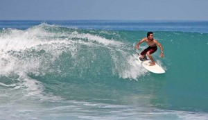 Local Indonesian surfer riding a big wave at Afulu on Nias Island, Indonesia