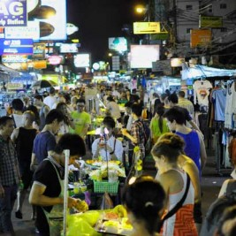 Khao San Road in Bangkok Thailand in the evening with tourists, food stalls, markets, and illuminating signs.