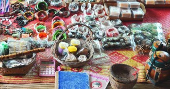 Tourist souvenirs such as wristbands, necklaces, finger rings, and soaps lying on a table for selling.
