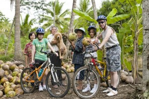 Biking tourists and locals posing at a coconut farm in Phuket, Thailand