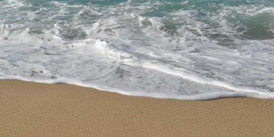 The white foamy ocean meets the golden sand on a Californian beach.