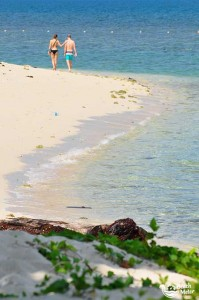 Young couple walking on the beach shore of Selingan Island of Borneo. Photo by Beachmeter.com.
