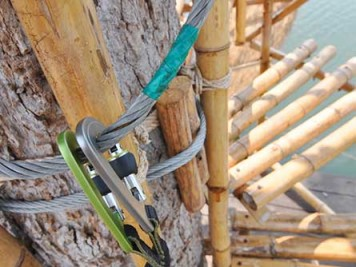 Two carabiners attached to a rope on a bamboo spiral stairway