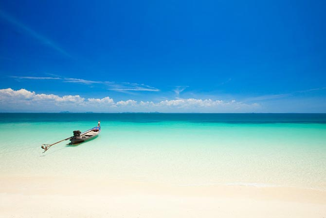 Lonely boat lying in the blue sea of Koh Kradan Island in Thailand, an island with stunning serene beaches.
