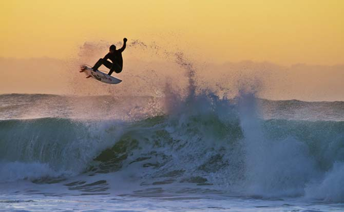 sunset surfing in new zealands Kahutara beach