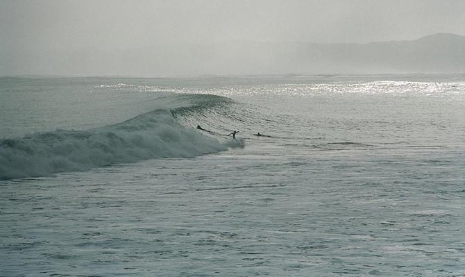 Surfers at Manu bay in New Zealand
